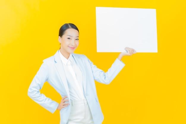 Retrato bela jovem asiática com outdoor branco vazio em amarelo