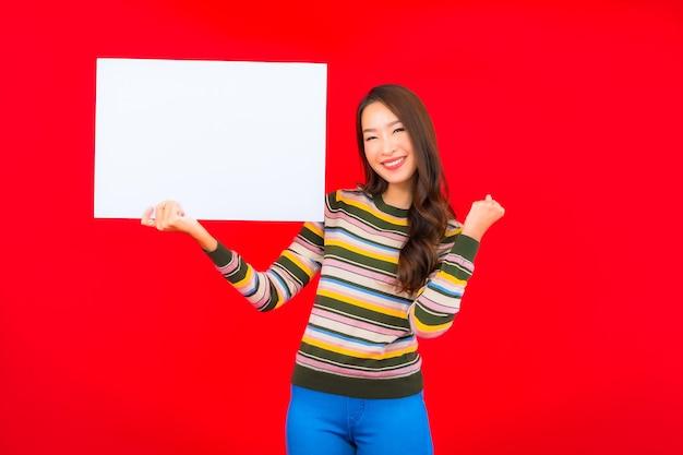 Retrato bela jovem asiática com outdoor vazio branco na parede vermelha