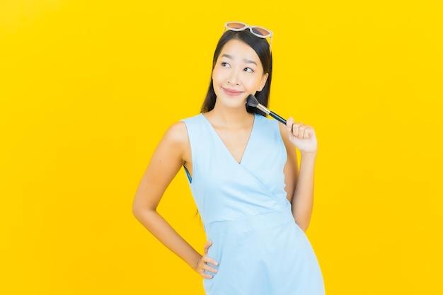 Retrato bela jovem asiática com pincel de maquiagem cosmético na parede de cor amarela