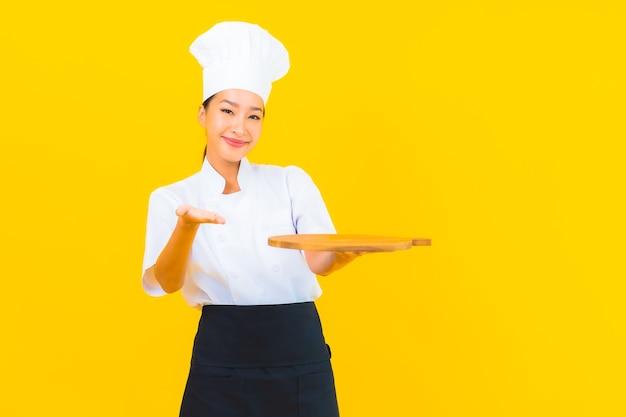 Retrato bela jovem asiática com uma tábua de madeira em fundo amarelo isolado.