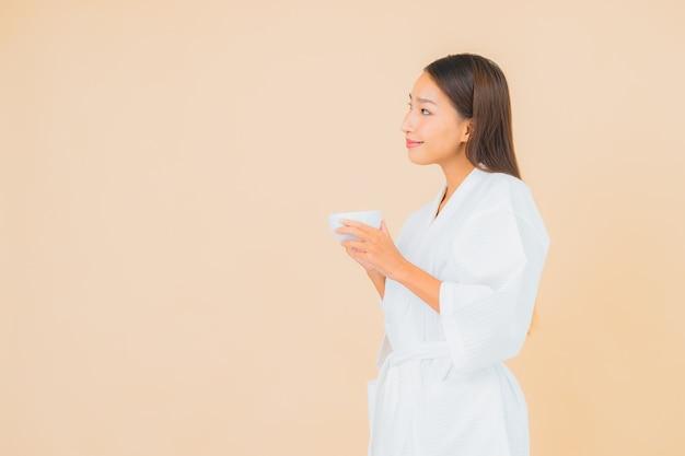 Retrato bela jovem asiática com xícara de café em bege