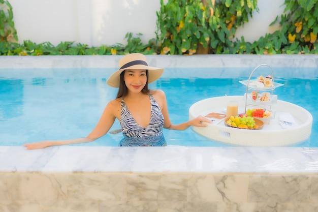 Retrato bela jovem asiática desfrutar com chá da tarde ou café da manhã flutuando na piscina