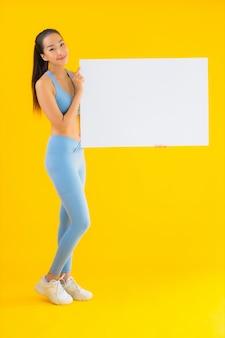 Retrato bela jovem asiática desgaste sportwear mostrar outdoor branco vazio amarelo