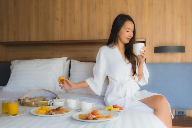 Retrato bela jovem asiática feliz desfrutar com café da manhã na cama no quarto