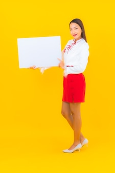 Retrato bela jovem asiática mostra outdoor vazio branco em amarelo isolado
