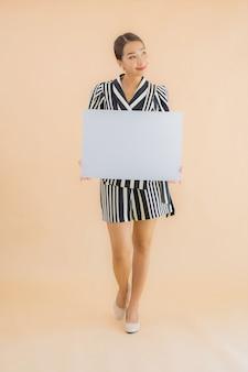 Retrato bela jovem asiática mostrar papel outdoor branco vazio