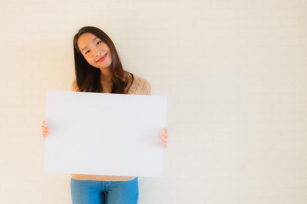 Retrato bela jovem asiática mostrar placa de papel branco em branco