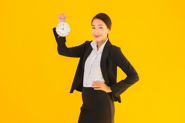 Retrato bela jovem asiática mostrar relógio ou alarme