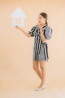 Retrato bela jovem asiática mostrar sinal de papel em casa ou casa
