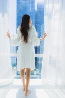 Retrato bela jovem asiática olhar fora da janela para a vista