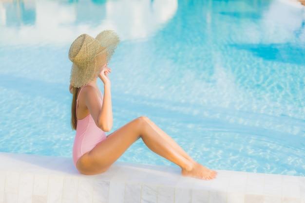 Retrato bela jovem asiática relaxando lazer ao redor da piscina ao ar livre com o mar