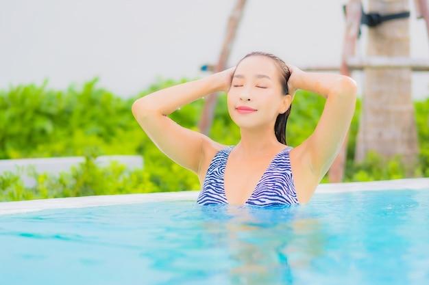 Retrato bela jovem asiática relaxando lazer ao redor da piscina com mar oceano praia