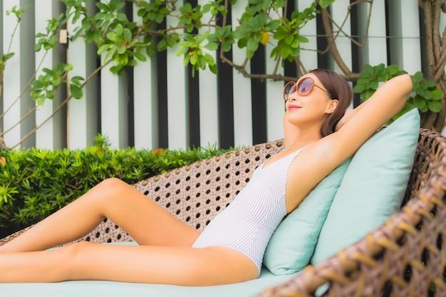 Retrato bela jovem asiática relaxando lazer ao redor da piscina em hotel resort para viagens de férias