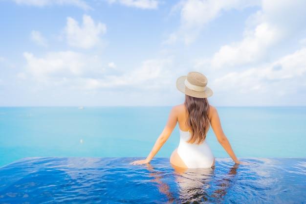 Retrato bela jovem asiática relaxando sorriso lazer ao redor da piscina ao ar livre com o mar oceano em viagens de férias