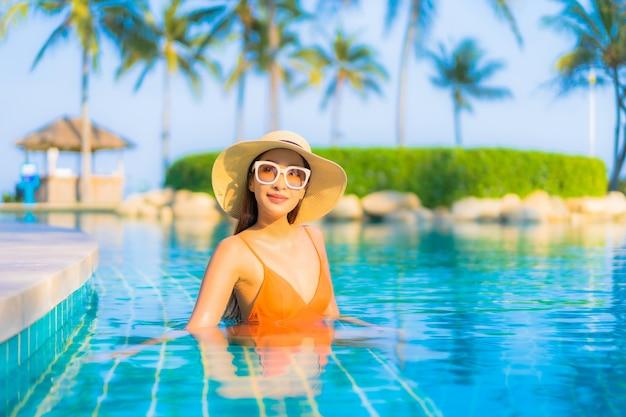 Retrato bela jovem asiática relaxando sorriso lazer ao redor da piscina ao ar livre com vista para o mar