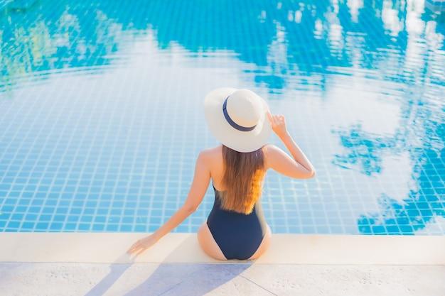 Retrato bela jovem asiática relaxando sorriso lazer ao redor da piscina ao ar livre perto do mar