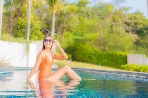 Retrato bela jovem asiática relaxando sorriso lazer ao redor da piscina em resort de hotel em viagens de férias