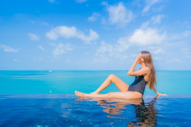 Retrato bela jovem asiática relaxando sorriso lazer ao redor da piscina em um hotel resort com vista para o mar