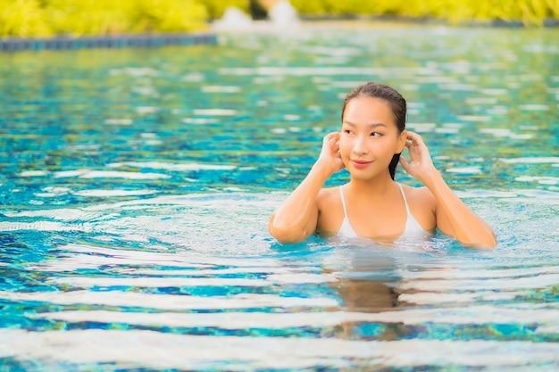 Retrato bela jovem asiática relaxando sorriso lazer ao redor de uma piscina ao ar livre perto do mar