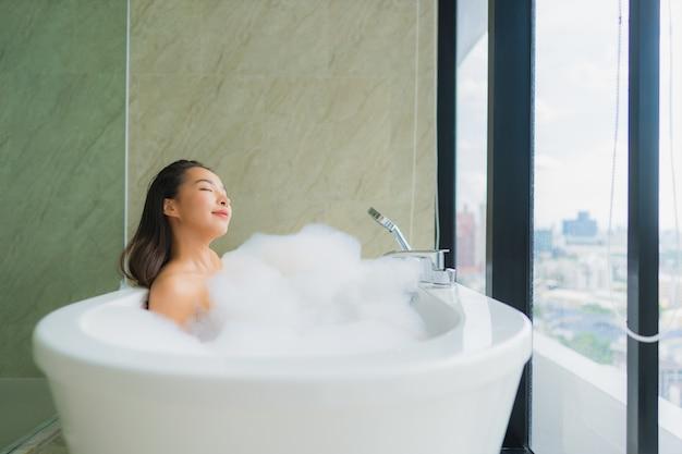 Retrato bela jovem asiática relaxar e lazer na banheira