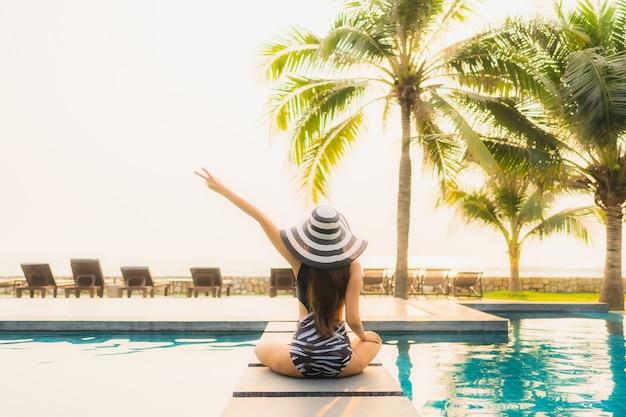 Retrato bela jovem asiática relaxar em torno da piscina no hotel resort com palmeira no pôr do sol ou nascer do sol