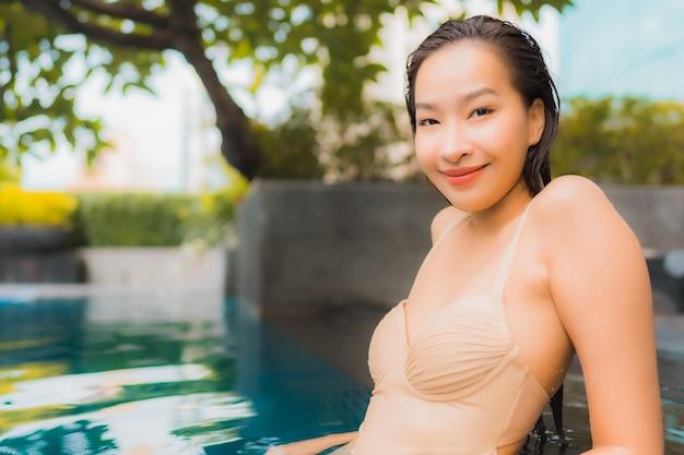 Retrato bela jovem asiática relaxar feliz sorriso lazer ao redor da piscina