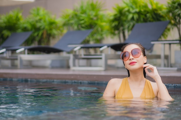 Retrato bela jovem asiática relaxar lazer ao redor da piscina
