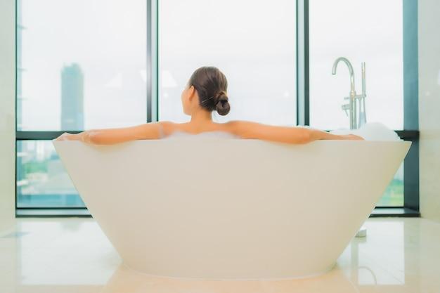 Retrato bela jovem asiática relaxar sorriso lazer na banheira no interior do banheiro