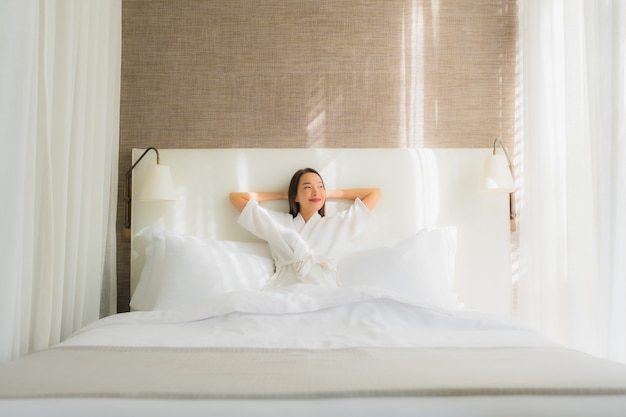 Retrato bela jovem asiática relaxar sorriso na cama no quarto