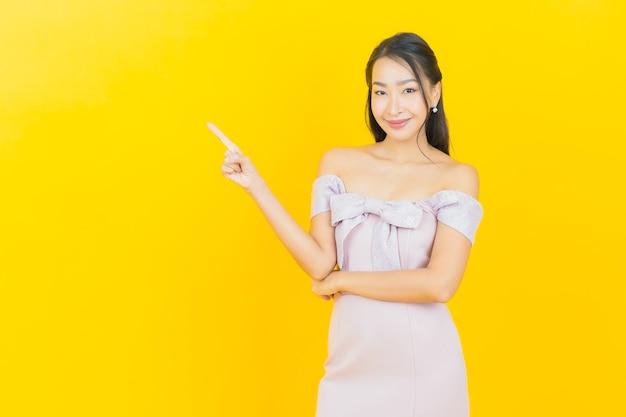 Retrato bela jovem asiática sorrindo e posando na parede colorida