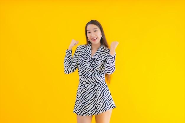 Retrato bela jovem asiática sorrir feliz com ação no amarelo