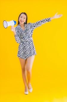 Retrato bela jovem asiática sorrir feliz com megafone em amarelo