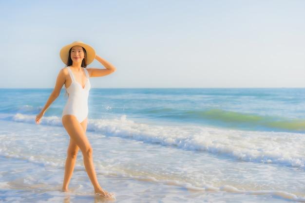 Retrato bela jovem asiática sorriso feliz ao redor da praia do mar oceano