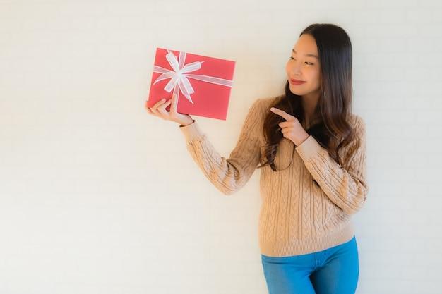 Retrato bela jovem asiática sorriso feliz com caixa de presente