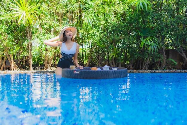 Retrato bela jovem asiática sorriso feliz com pequeno-almoço flutuante na bandeja na piscina