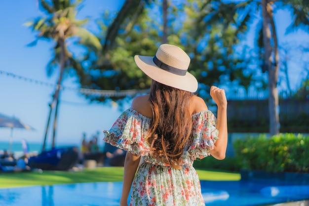 Retrato bela jovem asiática sorriso feliz relaxar ao redor do oceano praia tropical mar