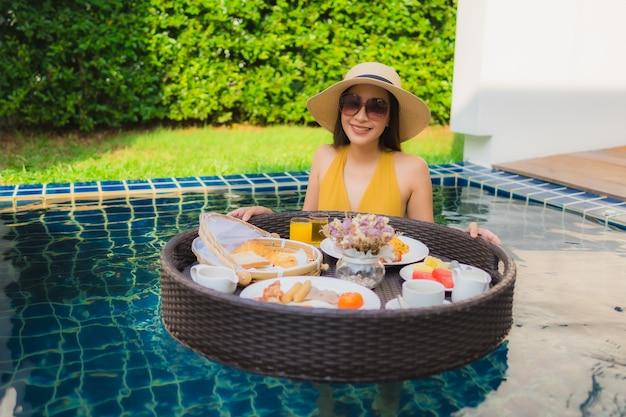 Retrato bela jovem asiática sorriso feliz relaxar com café da manhã flutuando em torno da piscina