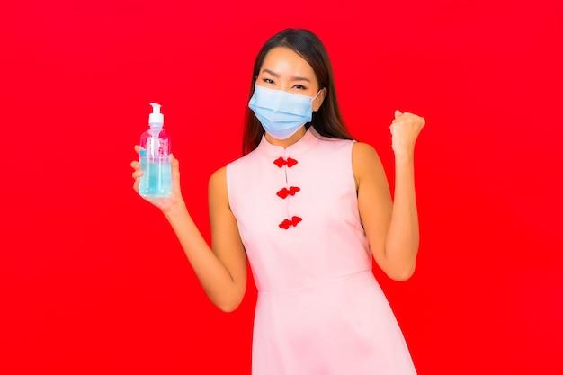 Retrato bela jovem asiática usa máscara para proteção contra covid19 e coronavírus na parede vermelha isolada