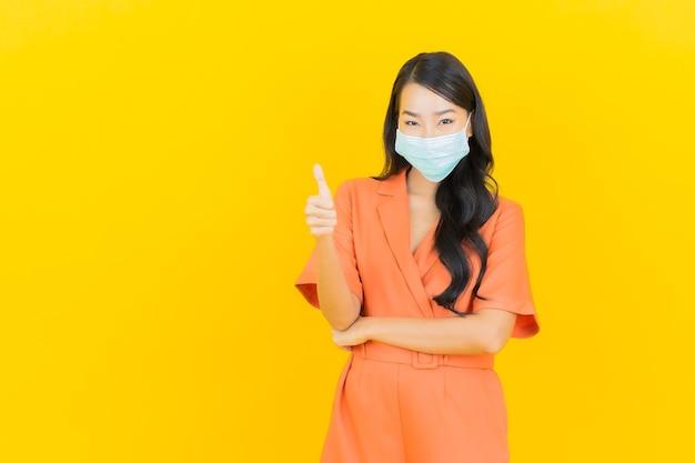 Retrato bela jovem asiática usa máscara para proteção covid19 em amarelo
