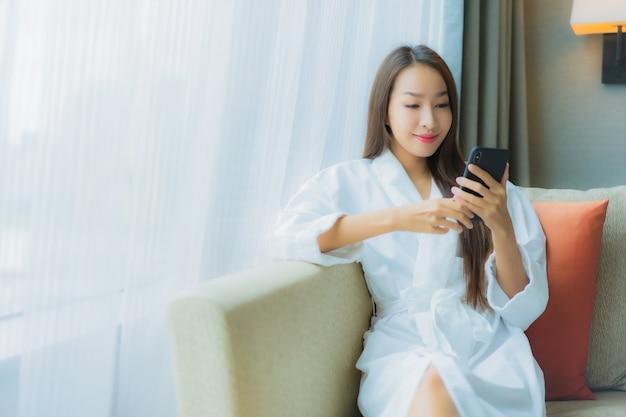 Retrato bela jovem asiática usando celular inteligente no sofá