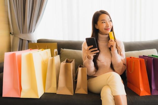 Retrato bela jovem asiática usando laptop ou celular móvel inteligente para compras on-line no sofá ao redor da sacola de compras