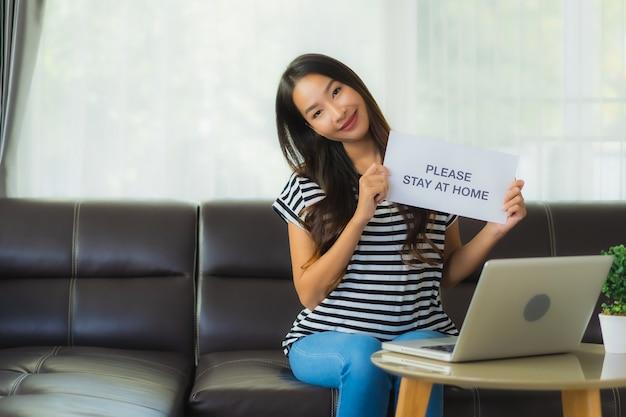 Retrato bela jovem asiática usando laptop ou computador noterbook no sofá com o conceito de trabalho em casa