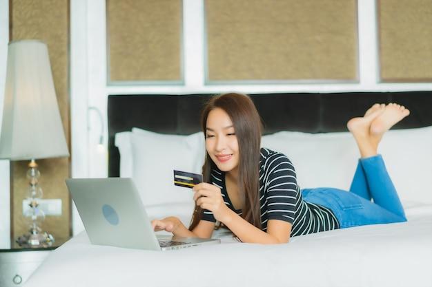 Retrato bela jovem asiática usando telefone celular inteligente com computador, laptop e cartão de crédito para fazer compras online
