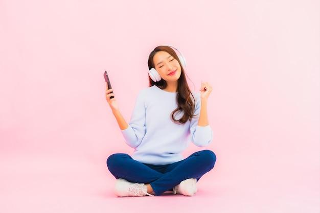 Retrato bela jovem asiática usando telefone celular inteligente com fone de ouvido para ouvir música na parede rosa