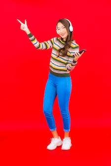 Retrato bela jovem asiática usando telefone celular inteligente com fone de ouvido para ouvir música