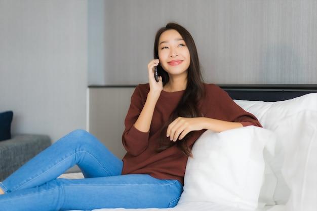 Retrato bela jovem asiática usando telefone celular inteligente na cama, no interior do quarto