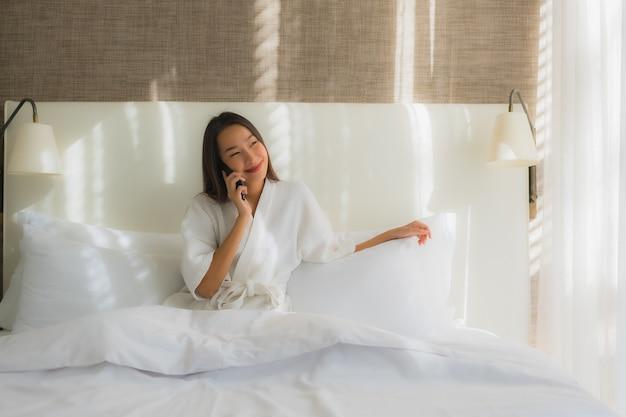Retrato bela jovem asiática usando telefone celular inteligente na cama no quarto