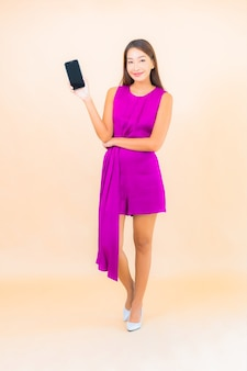 Retrato bela jovem asiática usando telefone celular inteligente na cor de fundo