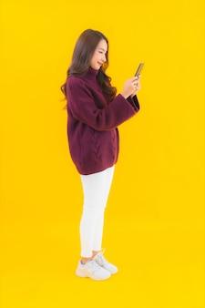 Retrato bela jovem asiática usando telefone celular inteligente