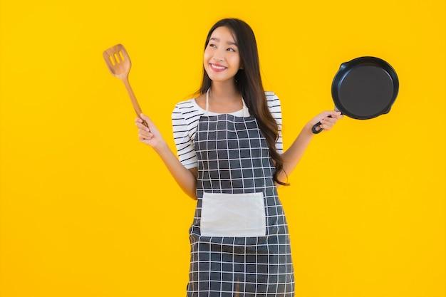 Retrato bela jovem asiática usar avental com panela preta e espátula